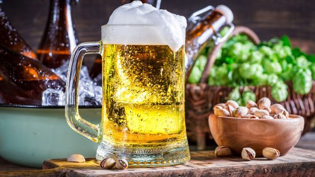 Ein gefülltes Bierglas mit einer Schale voller Pistazien