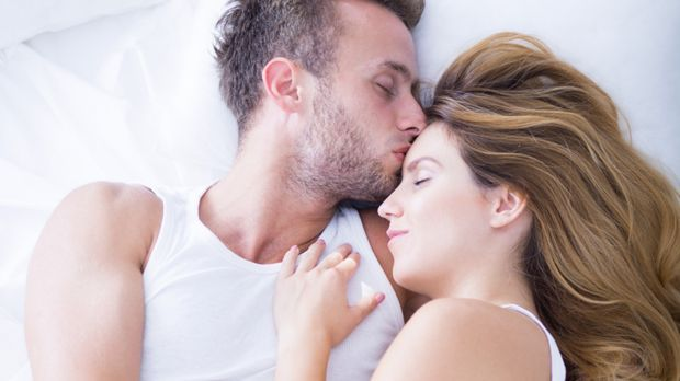 Pärchen liegt gemeinsam im Bett