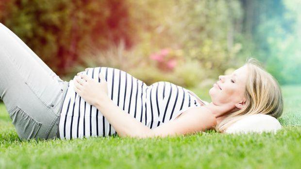 Schwangere liegt im Gras